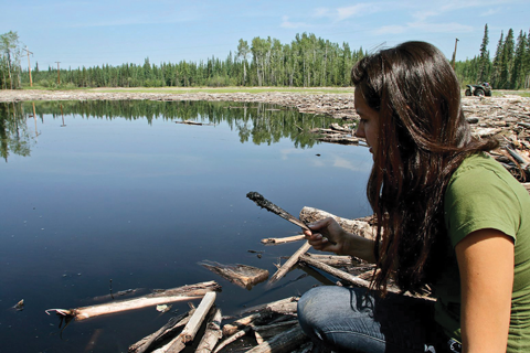 July 2011- Little Buffalo band member Melia Laboucan-Massimo scoops by oil from near the site of a Plains Midstream spill.