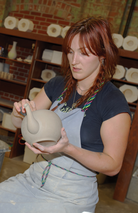 A worker trimming a teapot in the revitalized facility.