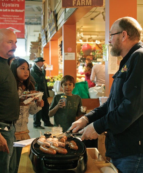 Ron Hamilton of Sunworks Farms cooks some organic beef sausage.